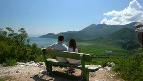 Το ζεύγος κάθεται σε έναν πάγκο και θαυμάζει την άποψη της λίμνης και των λόφων φιλμ μικρού μήκους