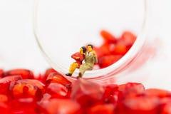 Το ζεύγος κάθεται στην άκρη ενός γυαλιού με ένα σύνολο γυαλιού της καρδιάς Στοκ Εικόνες
