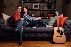 Το ζεύγος κάθεται στον καναπέ με μια κιθάρα Μακρυμάλλης ενός brunette με μια ακουστική κιθάρα Στοκ φωτογραφία με δικαίωμα ελεύθερης χρήσης