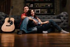 Το ζεύγος κάθεται στον καναπέ με μια κιθάρα Μακρυμάλλης ενός brunette με μια ακουστική κιθάρα Στοκ Φωτογραφίες