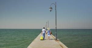 Το ζεύγος κερδίζει την κυλώντας τσάντα περπατώντας στην αποβάθρα απόθεμα βίντεο