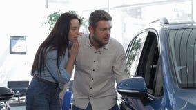 Το ζεύγος κοιτάζει μέσα στο μπλε SUV φιλμ μικρού μήκους