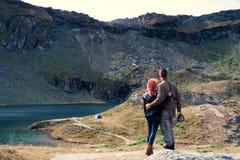Το ζεύγος κοιτάζει στην απόσταση στην κορυφή βουνών, λίμνη λάκκας Balea Διάστημα για το κείμενο, διακοπές στρατοπέδευσης σκηνών τ στοκ εικόνες