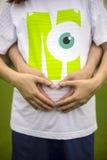 Το ζεύγος κρατά τα χέρια τους στο tummy, αναμένοντας το μωρό τους Στοκ Φωτογραφίες