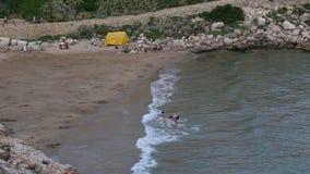 Το ζεύγος λούζει στη θάλασσα στην άγρια παραλία απόθεμα βίντεο