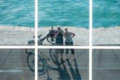 Το ζεύγος με τα ποδήλατα απεικονίζεται στα παράθυρα Στοκ Εικόνες
