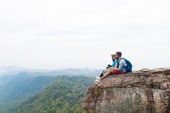 Το ζεύγος με τα σακίδια πλάτης κάθεται το αγκάλιασμα στην κορυφή βουνών απολαμβάνει το τοπίο, το νεαρό άνδρα και τον τουρίστα γυν στοκ φωτογραφία με δικαίωμα ελεύθερης χρήσης