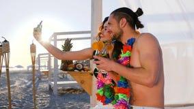 Το ζεύγος με το στεφάνι ανθίζει στο λαιμό που φωτογραφίζεται στη συσκευή, τον τύπο selfi και το κορίτσι από ένα εξωτικό θέρετρο, απόθεμα βίντεο