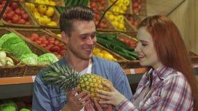 Το ζεύγος μυρίζει τον ανανά στην υπεραγορά στοκ εικόνα με δικαίωμα ελεύθερης χρήσης