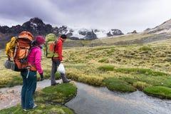 Το ζεύγος ορειβατών βουνών προετοιμάζεται να διασχίσει ένα μικρό ρεύμα βουνών στις Άνδεις στο Περού Στοκ Φωτογραφία