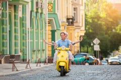 Το ζεύγος οδηγά το κίτρινο μηχανικό δίκυκλο Στοκ Φωτογραφία