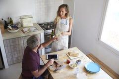 Το ζεύγος πίνει το κρασί και προετοιμάζει τα τρόφιμα στην κουζίνα, ανυψωμένη άποψη Στοκ Φωτογραφίες