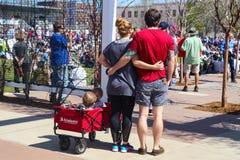 Το ζεύγος που αντιπροσωπεύει πίσω στη κάμερα με τα όπλα γύρω από ένα ένα άλλα και δύο παιδιά στο βαγόνι εμπορευμάτων στο Μάρτιο τ στοκ φωτογραφία με δικαίωμα ελεύθερης χρήσης