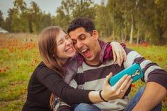 Το ζεύγος που κάνει τα ανόητα και αστεία πρόσωπα παίρνοντας selfie απεικονίζει το W Στοκ φωτογραφία με δικαίωμα ελεύθερης χρήσης