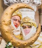 Το ζεύγος που ντύνεται στα σεληνιακά κοστούμια θέτει στη Βενετία καρναβάλι Στοκ Εικόνα
