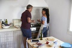 Το ζεύγος που προετοιμάζει τα τρόφιμα πίνει μαζί το κρασί από το φούρνο Στοκ Εικόνες