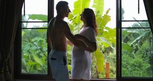 Το ζεύγος που στέκονται κοντά στο αγκάλιασμα παραθύρων που κοιτάζει στην άποψη πρωινού, ο άνδρας και η γυναίκα αγκαλιάζουν στην κ φιλμ μικρού μήκους