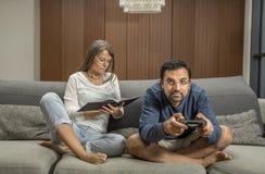 Το ζεύγος σε έναν καναπέ, άνδρας παίζει τα τηλεοπτικά παιχνίδια ενώ ανάγνωση γυναικών Στοκ φωτογραφία με δικαίωμα ελεύθερης χρήσης