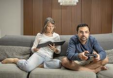 Το ζεύγος σε έναν καναπέ, άνδρας παίζει τα τηλεοπτικά παιχνίδια ενώ ανάγνωση γυναικών Στοκ Φωτογραφίες