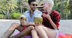 Το ζεύγος στην παραλία πίνει το κοκτέιλ καρύδων που μιλά κάθεται στο πλαίσιο των φοινίκων, του ευτυχών άνδρα και της επικοινωνίας φιλμ μικρού μήκους