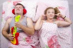 Το ζεύγος στον κρεβάτι-σύζυγο παίζει την κιθάρα, η σύζυγος κάλυψε τα δάχτυλά της στα αυτιά του Στοκ Φωτογραφίες