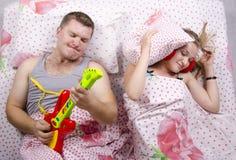 Το ζεύγος στον κρεβάτι-σύζυγο παίζει την κιθάρα, η σύζυγος κάλυψε το μαξιλάρι της Στοκ φωτογραφία με δικαίωμα ελεύθερης χρήσης