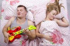 Το ζεύγος στον κρεβάτι-σύζυγο παίζει την κιθάρα, οι ύπνοι συζύγων Στοκ εικόνα με δικαίωμα ελεύθερης χρήσης