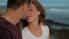 Το ζεύγος στο βλαστό φωτογραφιών στο περπάτημα παραλιών, που φιλά, απολαμβάνει τις στιγμές απόθεμα βίντεο