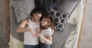 Το ζεύγος στο κρεβάτι είναι ομιλία, κρατώντας τα χέρια απολαμβάνοντας το χρόνο από κοινού απόθεμα βίντεο