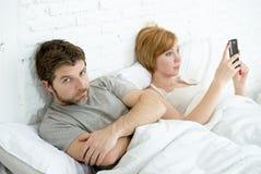 Το ζεύγος στο σύζυγο κρεβατιών ματαίωσε ανατρεμμένος και ανικανοποίητος ενώ το ζεύγος Διαδικτύου του στο σύζυγο κρεβατιών που ματ Στοκ Εικόνες