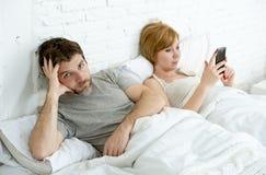 Το ζεύγος στο σύζυγο κρεβατιών που ματαιώθηκε ανέτρεψε ανικανοποίητο ενώ σύζυγος χρησιμοποιώντας το κινητό τηλέφωνο Στοκ Εικόνες