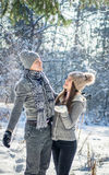 Το ζεύγος τινάζει τον κλάδο έλατου με το χιόνι Στοκ εικόνα με δικαίωμα ελεύθερης χρήσης