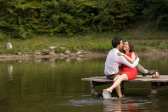 Το ζεύγος των ανθρώπων ερωτευμένων κάθεται στη γέφυρα Στοκ Εικόνες