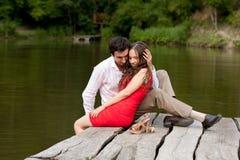 Το ζεύγος των ανθρώπων ερωτευμένων κάθεται στη γέφυρα Στοκ Εικόνα