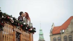 Το ζεύγος των εραστών αγκαλιάζει με σας Στέκονται στο ξύλινο μπαλκόνι κατά τη διάρκεια του χρόνου Χριστουγέννων καλή χρονιά απόθεμα βίντεο