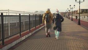Το ζεύγος των νέων φορά το kigurumi και τα παλτά, περπατώντας πέρα από το ανάχωμα απόθεμα βίντεο