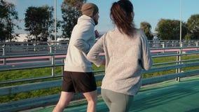 Το ζεύγος των νέων sportspersons τρέχει στη διαδρομή του ολυμπιακού σταδίου φιλμ μικρού μήκους