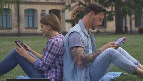 Το ζεύγος των σπουδαστών κάθεται πλάτη με πλάτη στο χορτοτάπητα στοκ εικόνες