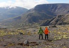 Το ζεύγος των τουριστών είναι στο οροπέδιο και θαυμάζει τα βουνά Στοκ Εικόνες