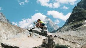 Το ζεύγος των τουριστών κάθεται σε έναν βράχο και μελετά έναν χάρτη εγγράφου, προγραμματίζει μια διαδρομή σε ένα πεζοπορώ βουνών στοκ εικόνες