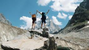 Το ζεύγος των τουριστών με τα σακίδια πλάτης στην εκστρατεία αυξάνει τα χέρια τους επάνω στην κορυφή των βουνών Έννοια της νίκης στοκ εικόνες με δικαίωμα ελεύθερης χρήσης