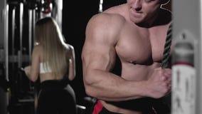 Το ζεύγος των bodybuilders στο τραίνο γυμναστικής οπλίζει triceps τους μυς χρησιμοποιώντας τη μηχανή καλωδίων απόθεμα βίντεο