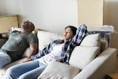 Το ζεύγος χαλαρώνει μετά από κινημένος μέσα προς το καινούργιο σπίτι στοκ εικόνες