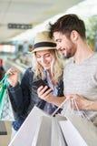 Το ζεύγος χρησιμοποιεί τις αγορές App για τη σύγκριση τιμών Στοκ Εικόνες