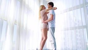 Το ζουμ μέσα της αγάπης του ζεύγους στις πυτζάμες που αγκαλιάζουν κοντά σε μεγάλο το παράθυρο απόθεμα βίντεο