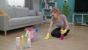 Το ζουμ μέσα της νέας κουρασμένης γυναίκας σκουπίζει το πάτωμα με την προσπάθεια φιλμ μικρού μήκους
