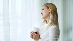 Το ζουμ στην ευτυχή νέα παντρεμένη γυναίκα πίνει τα όνειρα τσαγιού και ημέρας μπροστά από το παράθυρο απόθεμα βίντεο