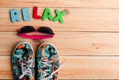 το ζωηρόχρωμα παπούτσι και τα γυαλιά ηλίου καμβά με RELAX το αλφάβητο στο W Στοκ Εικόνες