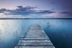 Το ζωηρόχρωμο τοπίο με τον ουρανό και την ξύλινη αποβάθρα λιμενοβραχιόνων απεικόνισε στη λίμνη στο βράδυ Στοκ Εικόνα