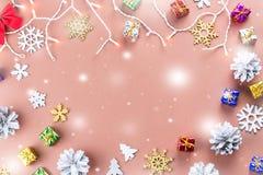 Το ζωηρόχρωμο υπόβαθρο Χριστουγέννων με τους κώνους κωνοφόρων, snowflakes, παρουσιάζει και Χριστουγέννων φω'τα σε ένα θερμό υπόβα Στοκ Εικόνες